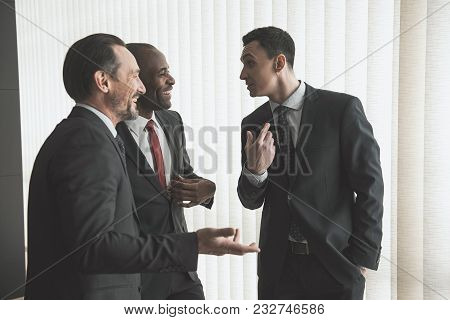 Three Employees Standing Near Window And Talking And Gesticulating. Jalousie On Background