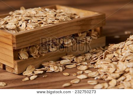 Oatmeal Flakes, Close-up. Dry Rolled Oat Flakes Oatmeal In A Glass Jar And Wood Box On An Old Wooden