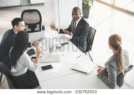 Team Of Young Professionals Sitting At Desk In The Meeting Room And Talking. Top View