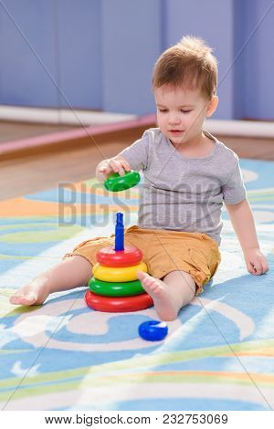The Small Child Collects A Pyramid Sitting On A Carpet