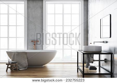 Luxury Bathroom Interior Idea. A Wooden Floor, A Large Window And A White Bathtub And Sink. Concrete