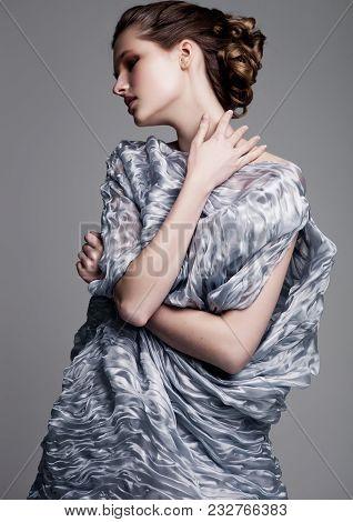Beautiful Fashion Model Wearing High Couture Silk Light Blue Dress On Grey Background