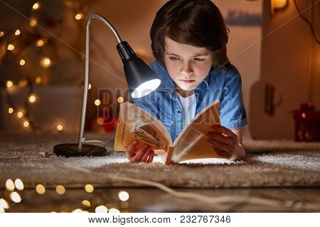 Waist up portrait of engaged boy keening on fascinating fairy tale. He is in nice comfortable nursery at home poster