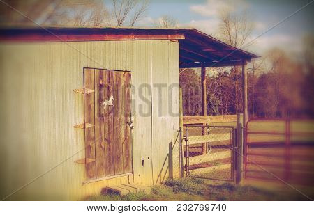 A Memory Concept Of An Old Rustic Barn With A Horse Emblem On A Prominent Wooden Door And A Fenced C