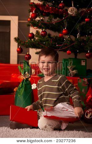 Portrait of little Boy sitting on Floor Weihnachtsbaum und Geschenke, lächelnd.?