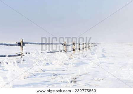 Beautiful Horizontal Image Of A Snow And Frost Covered Wooden Fence Running Into The  Foggy And Mist