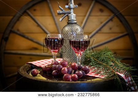 Horizontal Fine Art Image Of Two Glasses Of Red Wine Sitting On A Wood Barrel Adorned With Grapes An