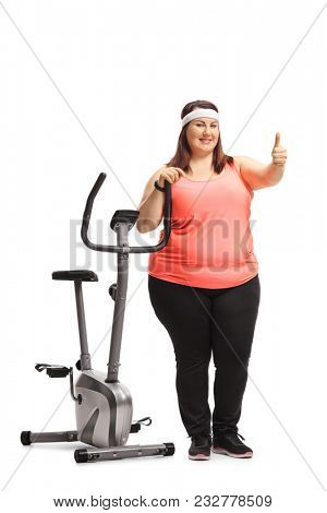 Full length portrait of an overweight woman leaning on an exercise bike and making a thumb up sign isolated on white background