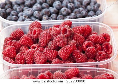 Red Raspberries. A Plastic Tray With Several Raspberries. Raspberry. Red-fruited Species Of Rubus Na