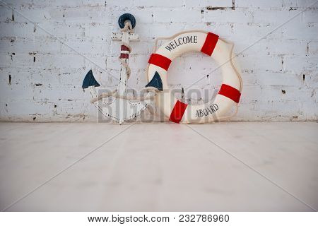 A Composition On A Sea Theme With An Anchor And Life Ring On A White Brick Wall