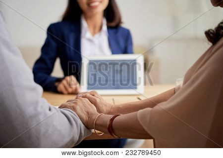 Close-up Shot Of Affectionate Senior Couple Holding Hands While Sitting At Office Of Estate Agent An