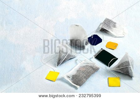 Several Tea Bags Of Different Shapes And With Different Kinds Of Tea On Light Blue Background. Tea B