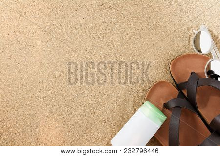 Vintage Brown Sandals And Sunblock And Sunglasses On Sand Of Beach From Top View