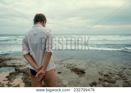 Sad Caucasian Woman In Shirt Stand On Beach. Back View. She Is Alone And Pensive. To Have Bad Mood D