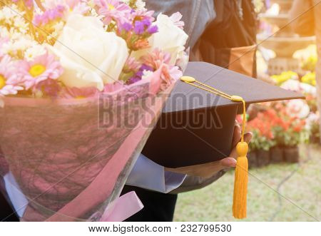 International Graduate Study Concept : Graduation Black Cap On Students Woman Hands With Flowers On