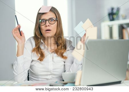 Beautiful tired and crazy mature businesswoman in glasses works in the office