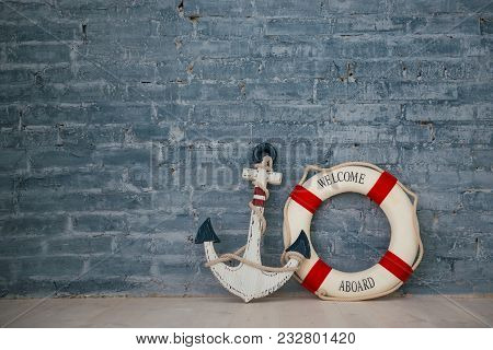 Composition On A Sea Theme With An Anchor And Life Ring On A Gray Brick Wall