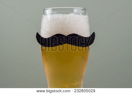 Glass With Beer And A Symbolic Black Mustache. Background - Olive Wall, Red-white Checked Tablecloth