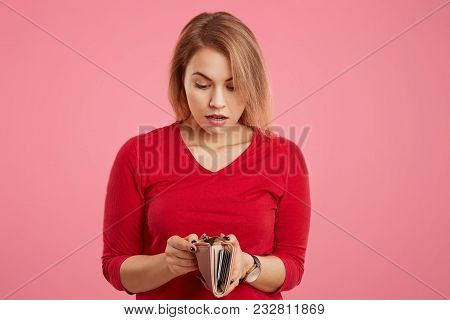 Surprised Female Model Being Short Of Money, Looks With Shocked Expression In Wallet, Has Not Enough