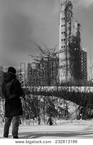 One Man Stands Against A Ruined Television Tower. Black And White Photo