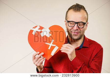 Healed Love. Valentines Day Concept. Adult Smiling Man Holding Big Red Heart With Plaster. Male Heal