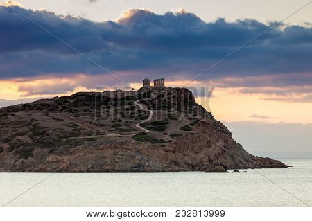 Greece Cape Sounion. Ruins Of An Ancient Temple Of Poseidon At Morning Sunrise, View From Distance.