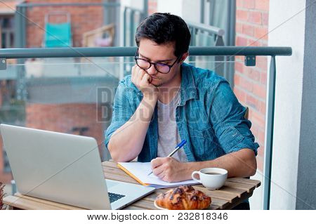 Young Handsome Man Sitting At A Table With Notebook Na Cup Of Coffee. Writing Something In A Note. L