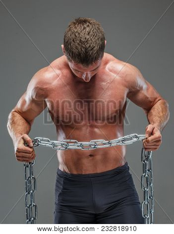 Musculed Bodybuilder Showing His Abs Holding Steel Chain
