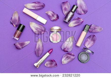 Set Of Decorative Cosmetics On A Violet Background With Petals. Flat Lay