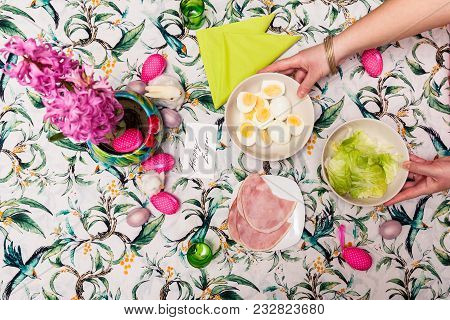 Top View Of Breakfast Table With Easter Meal And Woman Hand, Fried Eggs, Salad, Hams, Lilac Flower.