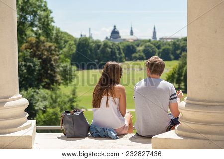Young Couple On A Date At Monopteros Monument Ejoying View Over Englischer Garten In Munich, Germany