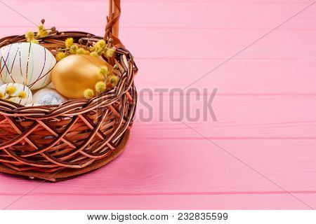 Easter eggs in wicker basket. Gold egg, decorated styrofoam egg and pussy willow in woven basket on pink wood, copy space. Happy Easter background. poster