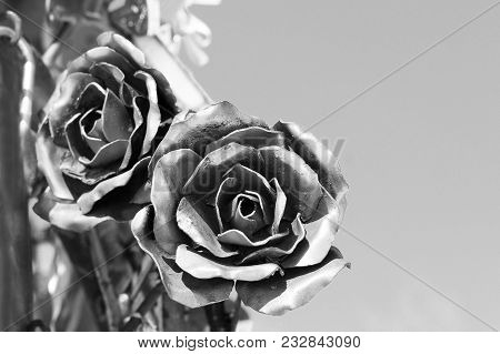 Two Metal Roses On A Background Of Blue Sky