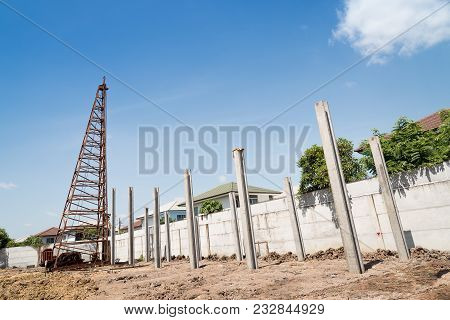 Pile driving machine with reinforced concrete piles on construction site. poster