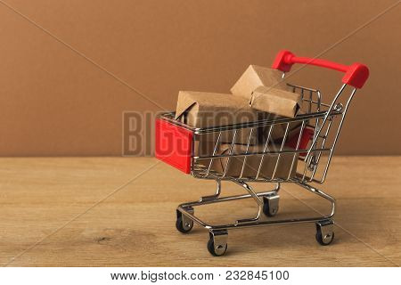 Miniature Toy Shopping Cart And Parcels On Brown Background, Business, Shopping Concept. Mockup For