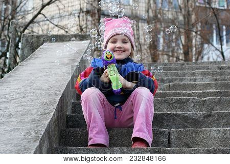 A Smiling Little Girl Is Sitting On The Steps And Blowing Soap Bubbles By A Bubble Blower. A Housing