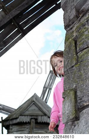 Beautiful Smiling Little Girl In A Pink Suit Is Peeking Out From Behind The House