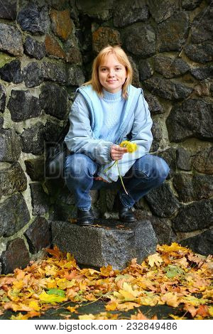 A Young Smiling Blonde Woman With Yellow Dandelions In Her Hands Is Squatting Near A Stone Wall. She