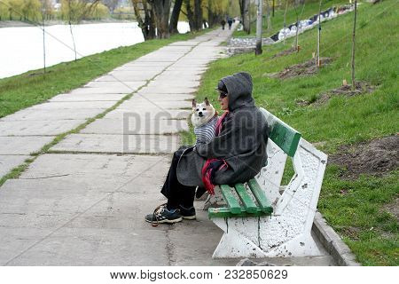 Kiev. Ukraine. 21.04.2007. A Woman In A Sunglasses Wearing In A Jacket With Hood Is Sitting On The B