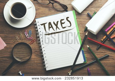 Taxes Text On Notebook With Coffee And Stationery Supplies On Table