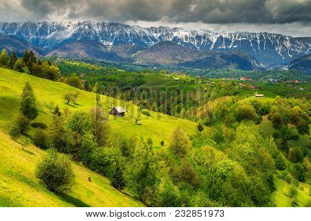 Majestic Alpine Landscape With Stunning Green Fields And High Snowy Piatra Craiului Mountains Near B