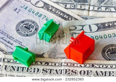 Overturned Miniature Houses On Top Of American Usd Dollar Currency Symbolising Expensive Houses And