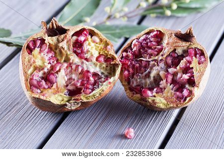 Pomegranate In Halves Over Wooden Table