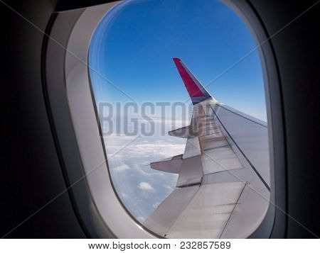 Airplane Wing Over Blue Sky And White Cloud View Looking Through Airplane Window. Travel, Vacation A