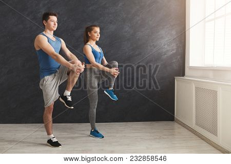 Couple Warming Up Legs Before Training, Standing Back To Back At Gym. Sporty Man And Woman Doing Str