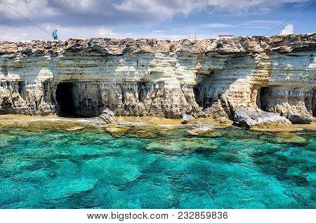Sea Caves Of Cavo Greco Cape. Ayia Napa, Cyprus With Men. Mediterranean Sea Landscape