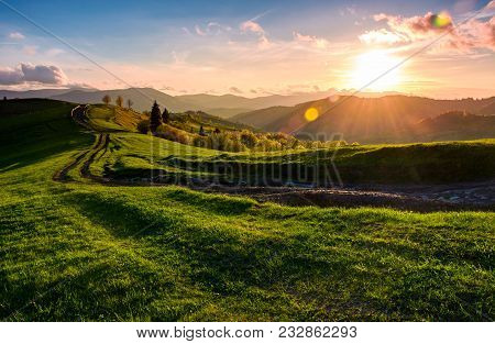 Winding Road Along The Grassy Rural Hill At Sunset. Gorgeous Landscape Of Carpathian Mountain In Spr