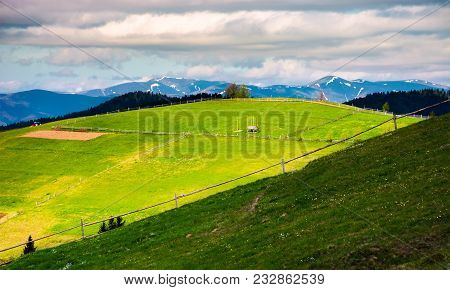 Fence On A Grassy Slope Of Carpathian Rural Area. Beautiful Landscape On A Cloudy Springtime Day