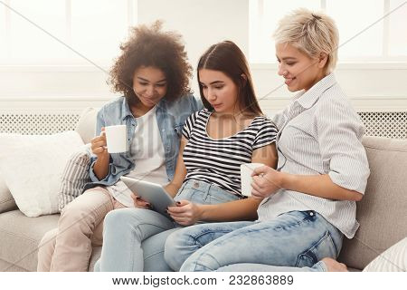 Three Happy Female Friends Using Digital Tablet And Drinking Coffee. Women Browsing Portable Compute