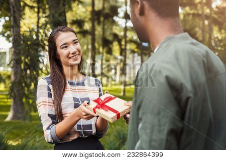 Young Asian Woman With Giftbox Surprising Her African-american Boyfriend With Anniversary Present, S